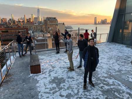 A man smiling and other museum goers on the rooftop of the Whitney Museum of American Art.