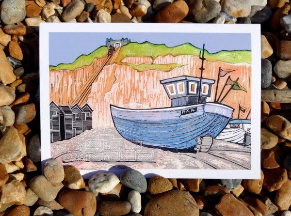 fishing boat linocut greetings card photo against pebbles