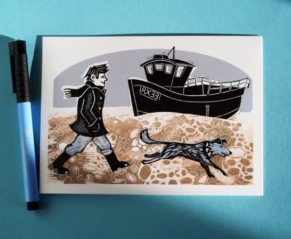 greetings card based on a linocut print of a man and dog walking on the beach beside a fishing boat