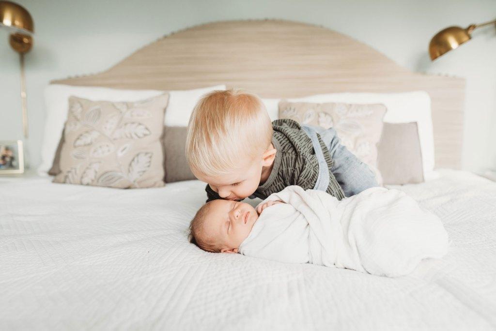 big brother kisses brand new newborn sister