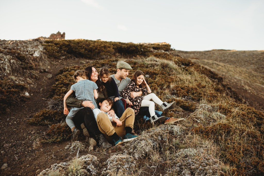 family snuggles on mountain top