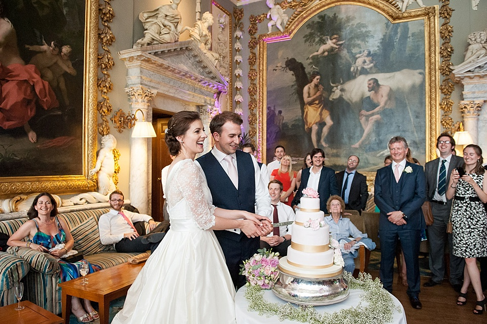 Wedding traditions   where they started   cake   champagne     Wedding traditions   capturing the moment   cutting the cake with gold  ribbon and pink flowers