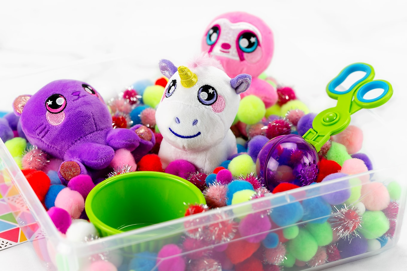 Squeezamals in a Pom Pom Sensory Bin With Cup and Scoopers