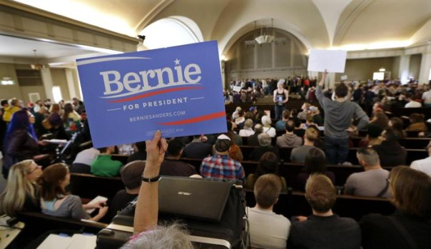 A Bernie Sanders supporter holds up a sign during a Democratic caucus Saturday, March 26, 2016, at Seattle's Town Hall. Democrats caucused statewide in support of either Hillary Clinton or Sanders. (ANSA/AP Photo/Elaine Thompson) [CopyrightNotice: Copyright 2016 The Associated Press. All rights reserved. This material may not be published, broadcast, rewritten or redistributed without permission.]