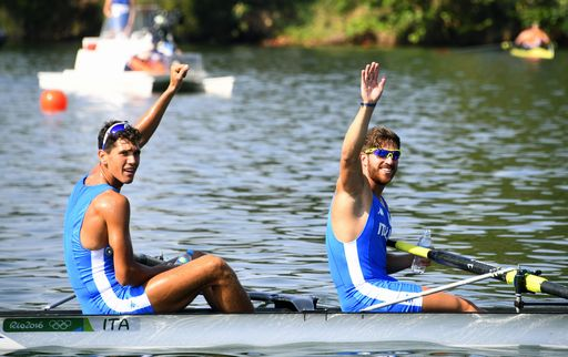 Italy's Marco di Costanzo and Italy's Giovanni Abagnale (L) wave after winning the Men's Pair Semifinal rowing competition at the Lagoa stadium during the Rio 2016 Olympic Games in Rio de Janeiro on August 9, 2016. / AFP PHOTO / Damien MEYER