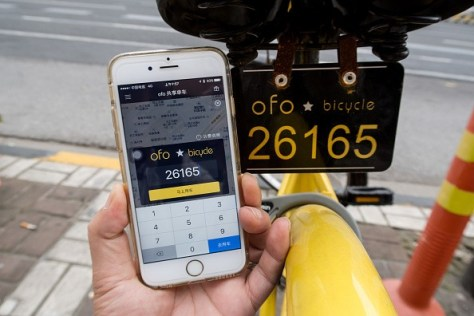 a-passenger-uses-app-on-the-phone-to-check-mileage-of-a-yellow-rental-bike-at-the-service-points-of-zhoujiazui-road