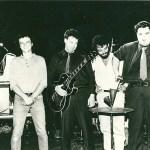 Pere Ubu - 1980, standing on stage. (l to r) Allen Ravenstine, Scott Krauss, Mayo Thompson, Tony Maimone, David Thomas.  Photo Credit: Rough Trade