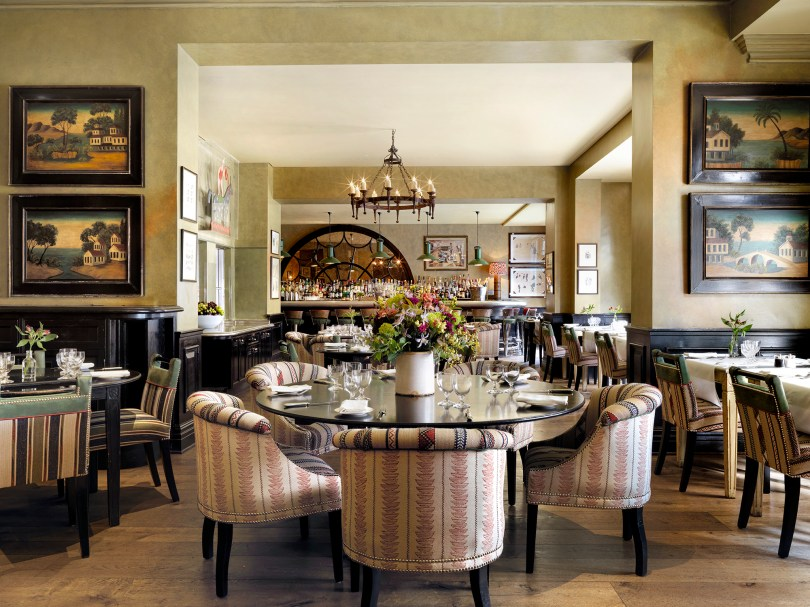 Brasserie Max restaurant with a round table surrounded by comfortable fabric chairs