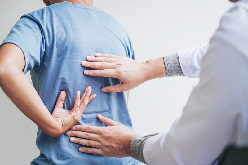 Doctor checking a patient's back for pain