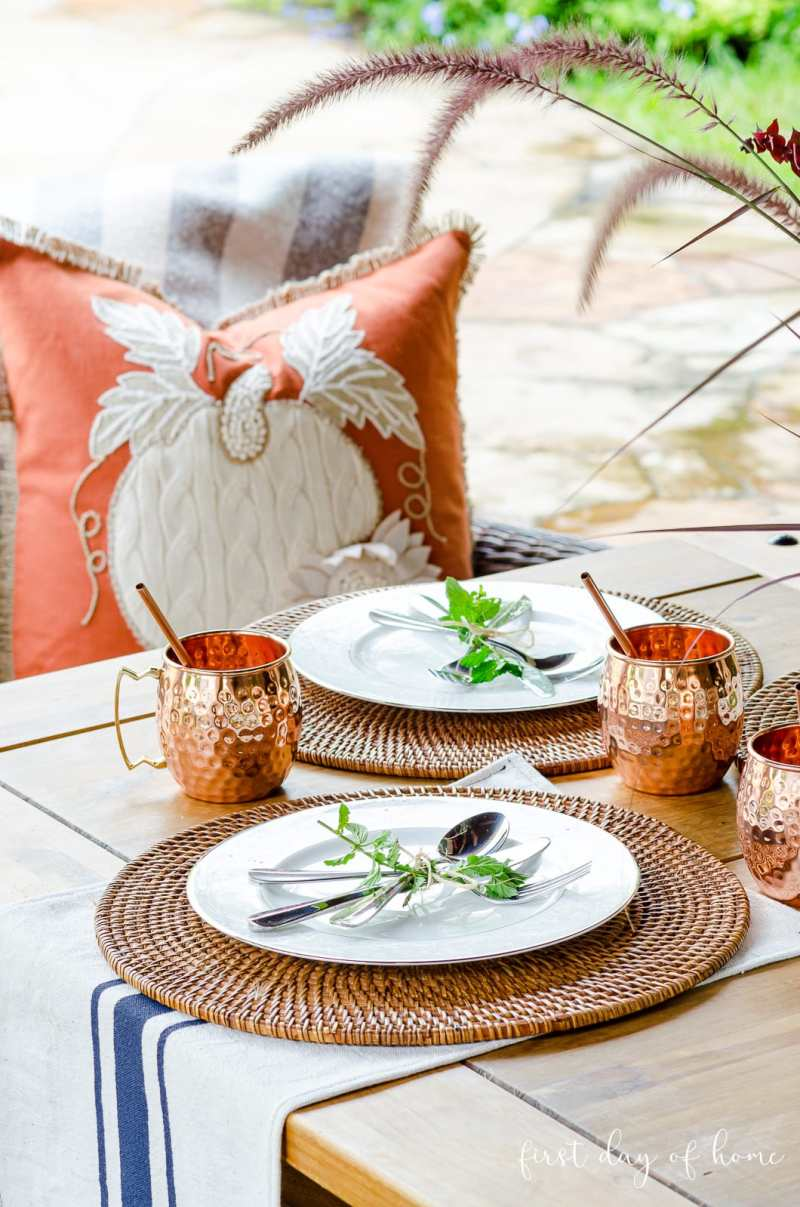 Fall tablescape with fresh mint on place setting, grain sack towel, copper mugs and orange throw pillow on furniture