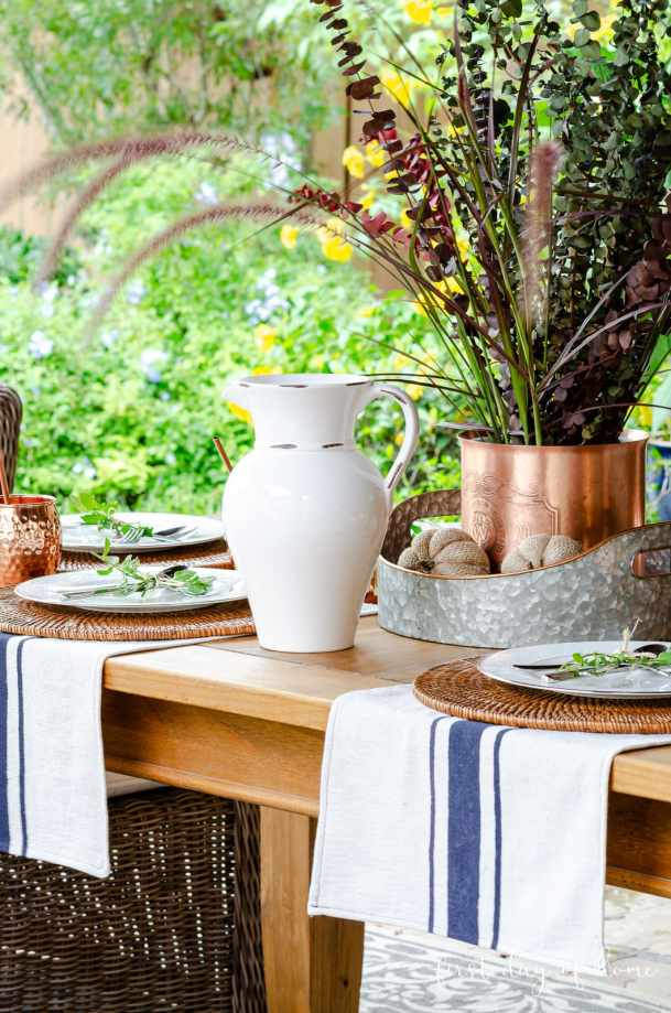 Fall outdoor table decor with grain sack towel and rustic fall centerpiece