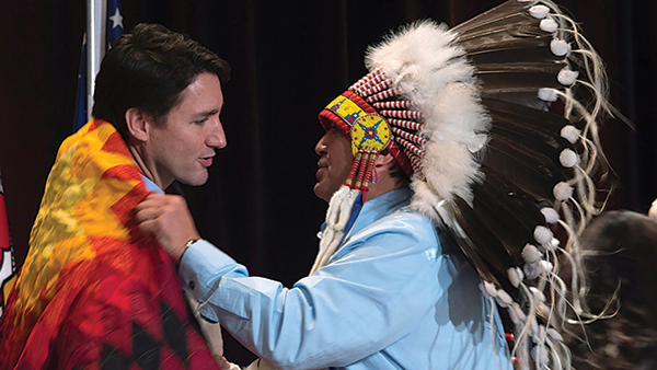 AFN National Chief Perry Bellegarde presents Prime Minister Justin Trudeau with a blanket in December 2015. (Picture courtesy of Adrian Wyld / THE CANADIAN PRESS via www.ctvnews.ca)