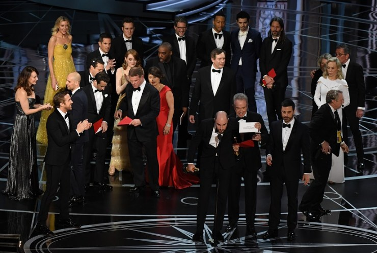 La La Land producer Jordan Horowitz (front C) shows the card saying Moonlight won the best picture as actor Warren Beatty (front 4R), and Host Jimmy Kimmel (3R) look on at the 89th Oscars. AFP