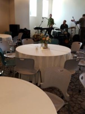 A band setting up to perform in entertainment space for a wedding reception