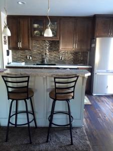 Rustic Alder Kitchen Cabinets with Tile Backsplash and a New Kitchen Island with a Raised Snack Bar and Cook Top
