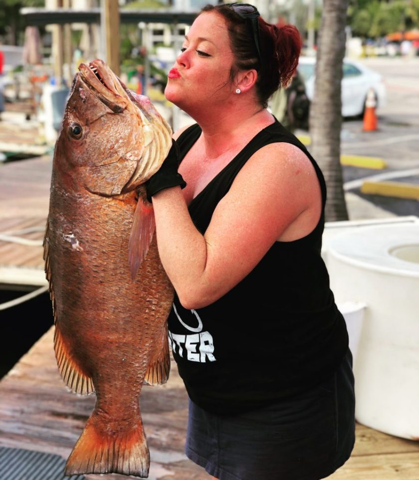 A fisher gal holding up the Cubera Snapper about to give it a big kiss.