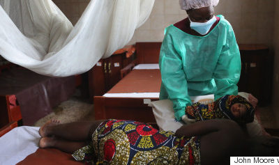 MONROVIA, LIBERIA - JANUARY 29:  Midwife Maima Johnson hands a newborn girl to mother Cecelia Mensah, 20, after delivering the child at the Star of the Sea Health Center on January 29, 2015 in the West Point township of Monrovia, Liberia. Midwives and health workers in the clinic have taken extra precautions throughout Liberia's Ebola epidemic to avoid becoming infected. The World Health Organization (WHO), announced that in the last week there were less than 100 new Ebola cases in West Africa, with a dramatic decrease in Liberia, where the numbers are in the single digits. The WHO said their focus has now shifted from slowing transmission to ending the epidemic.  (Photo by John Moore/Getty Images)