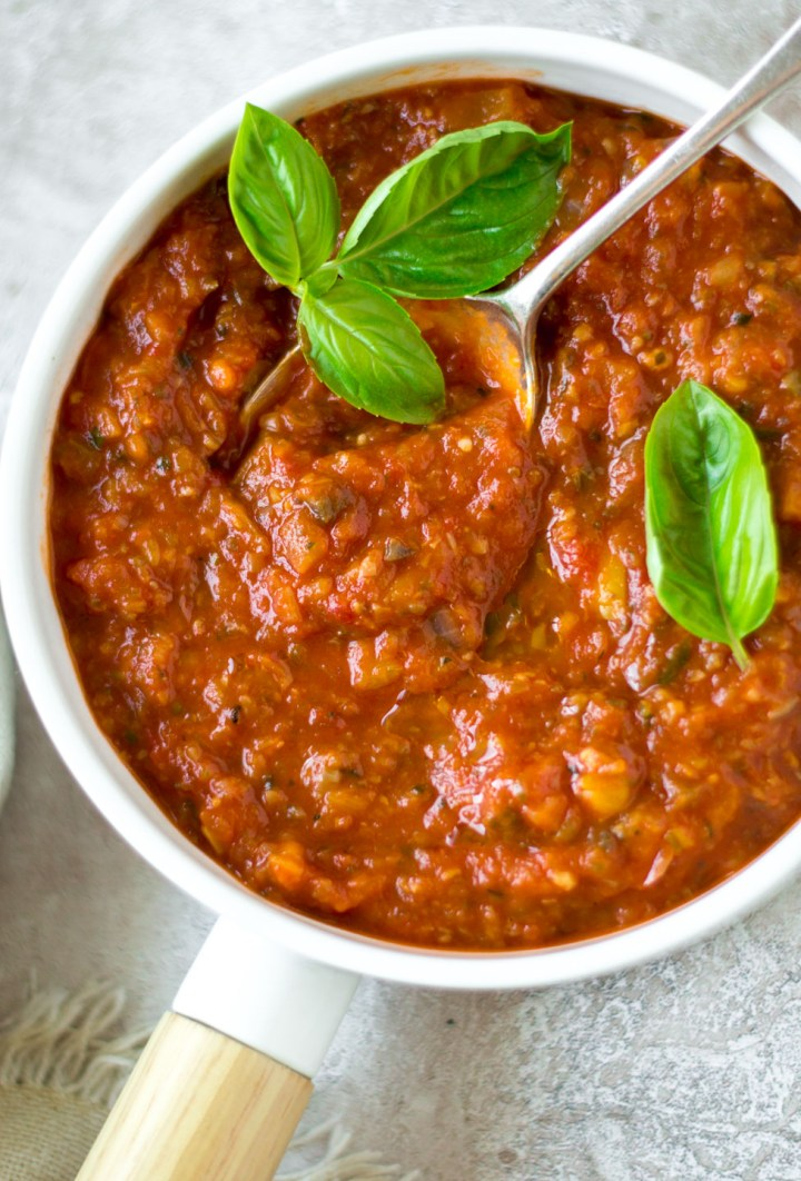 Top down view marinara sauce in a white dish with spoon and basil leaves