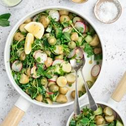 Vegan potato salad in a white bowl, top down view