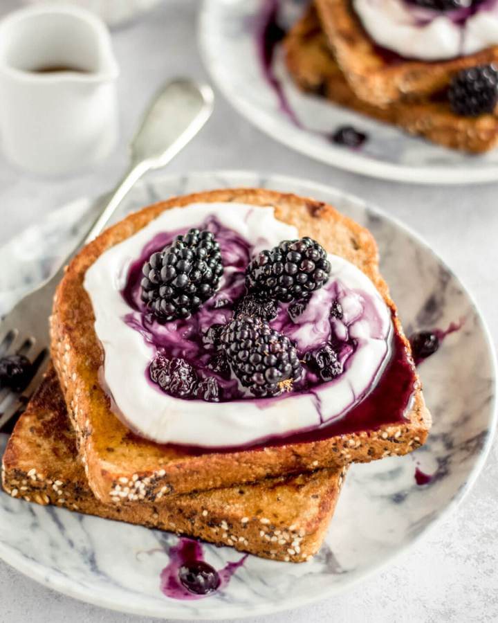 2 slices of Vegan French toast with yoghurt and berry compote on a grey plate