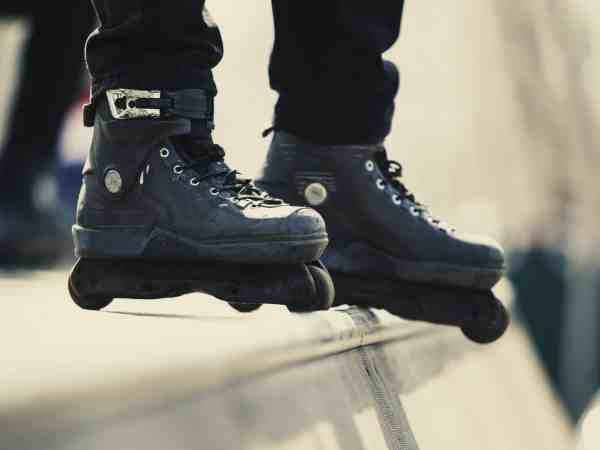 Aggressive inline roller blader stands on ramp top wearing black skates for extreme skating.Feet of young athlete in in-line blades exercising in skatepark outdoor in summer