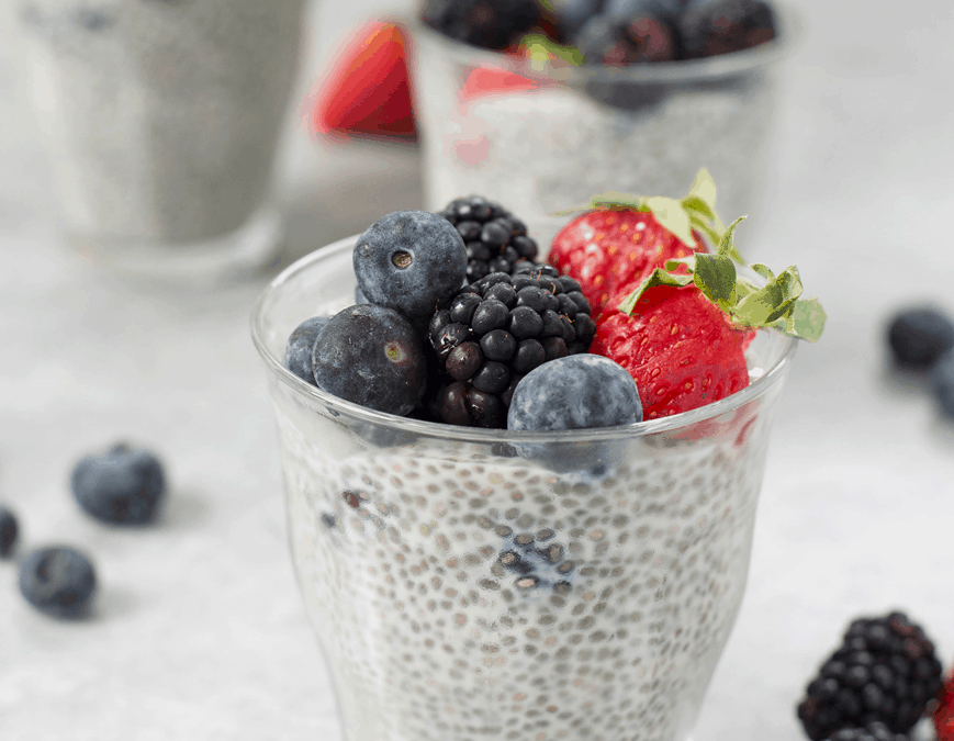 chia pudding with fruit on top in a clear glass container