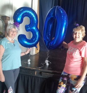 Two Fitness League women with 30th anniversary balloon