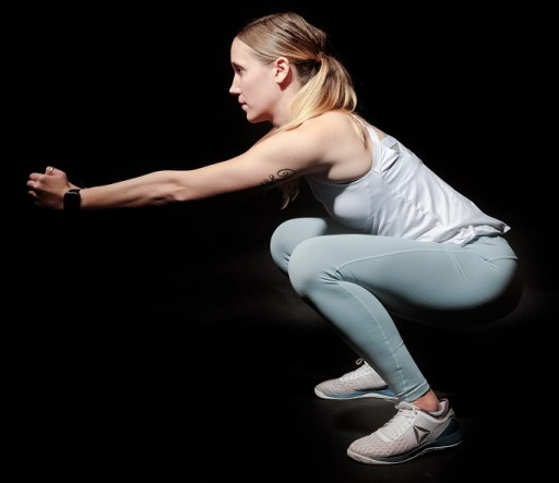 girl doing bodyweight squat at home