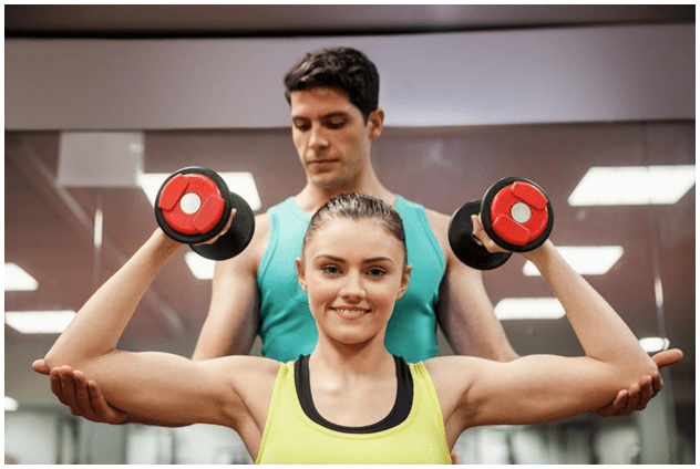 Man and woman doing exercise with dumbbells