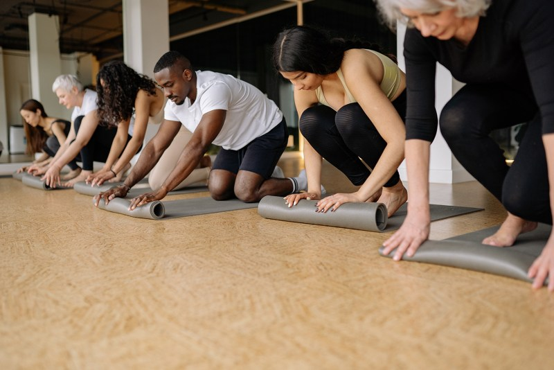 People Rolling Up Mats in a Fitness Studio