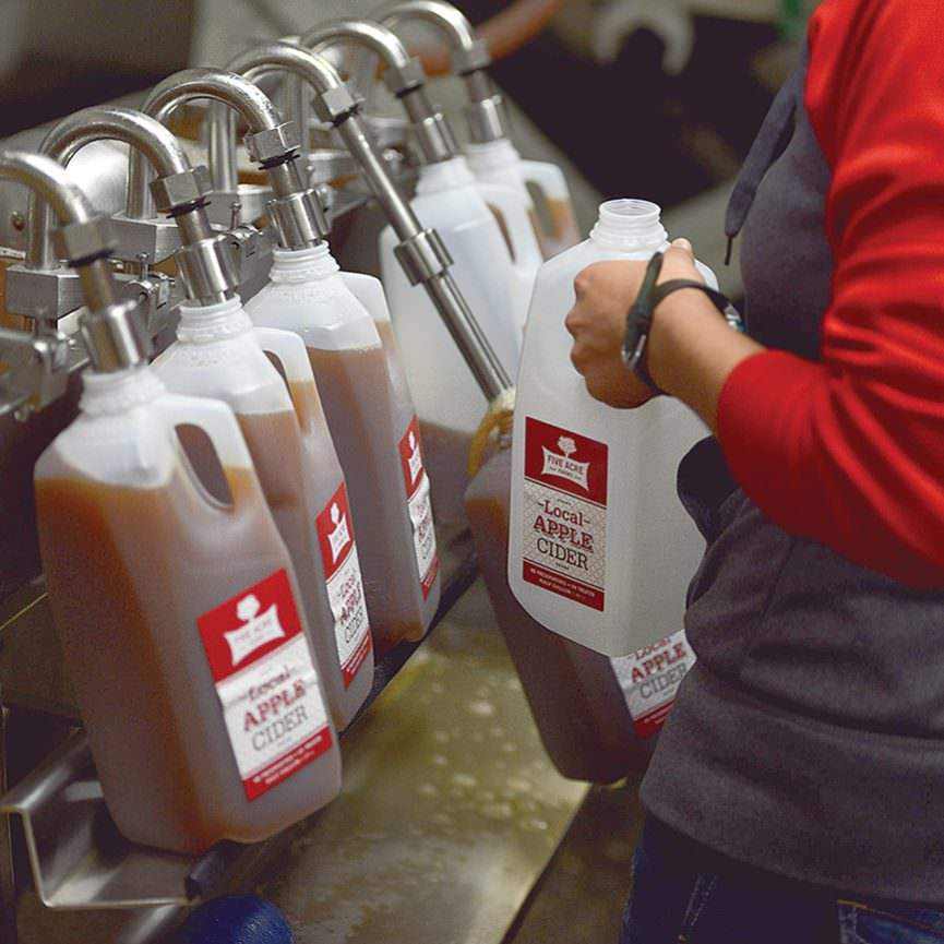 filling half gallons of cider - Five Acre Farms