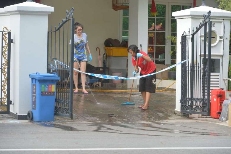 A lady and one of the maids (in red) washing blood stains off the porch floor at 50C Lorong H Telok Kurau on June 8, 2016.