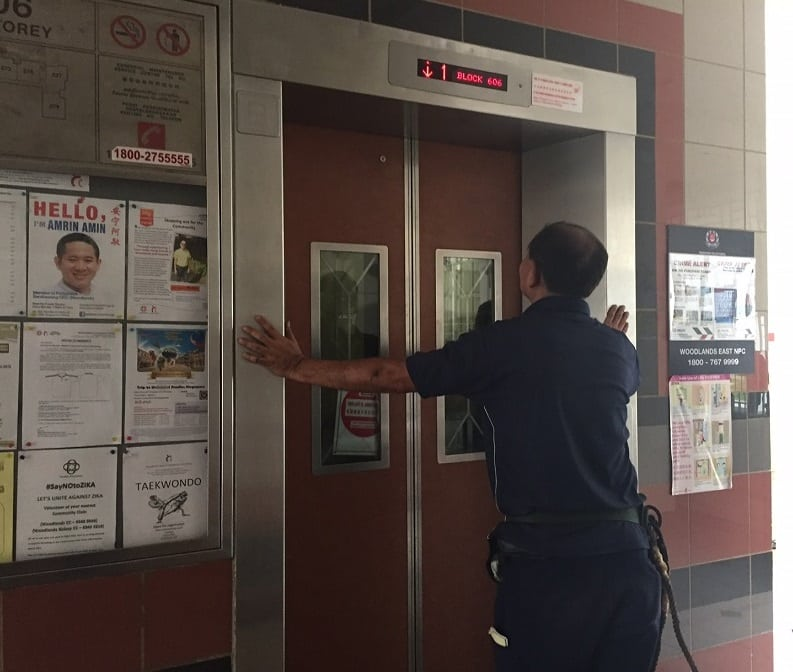 Lift technician removes lift maintenance sign