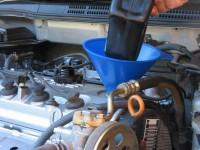 Add oil to the engine using a funnel for less mess.