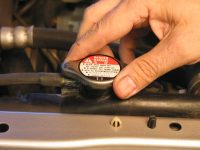 The coolant cap is on top of the radiator and/or coolant reservoir. When the engine is cool, twist to open.