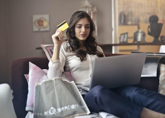 Junge Frau mit Kreditkarte am Computer