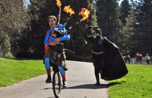 Batman Hilariously Unicycling And Superman Playing Flaming Bagpipes
