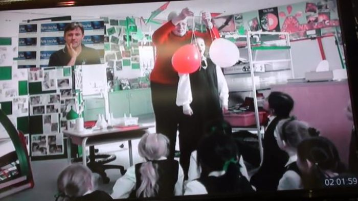 Blow em apart science experiment - student blowing apart balloons during a Fizzics video conference