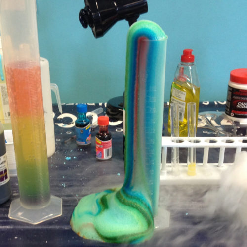 Colourful chemistry happening in beakers, measuring cylinders and more with dry ice fog as well