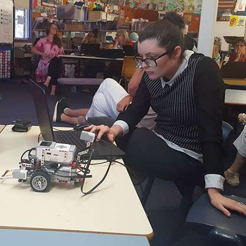 A teacher programming a Lego Mindstorms Robot