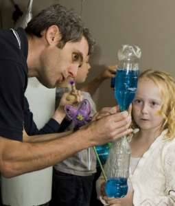 Tornado in a bottle science experiment - showing a young girl a blue tornado in a bottle