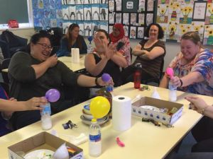 multiple teachers surrounding a table laughing whilst doing an experiment involing a balloon and a bottle