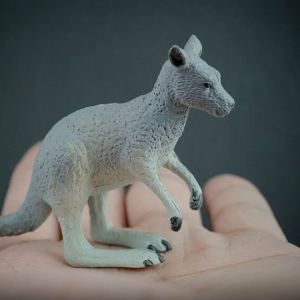 Eastern grey kangaroo replica placed in the palm of a hand. Side view