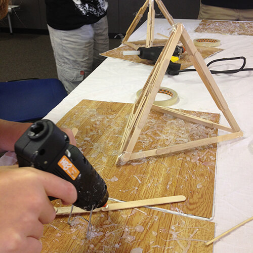 Create a catapult using hot glue and wooden sticks