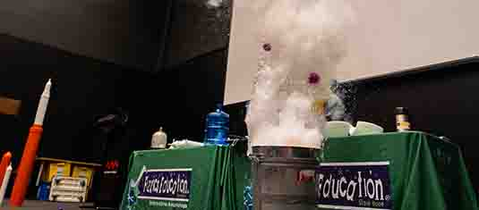 Water erupting from a bin in front of a science presentation desk