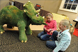 kids feeding a triceratops replica