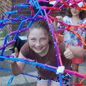 Girl inside a huge hoberman sphere during a kids science party