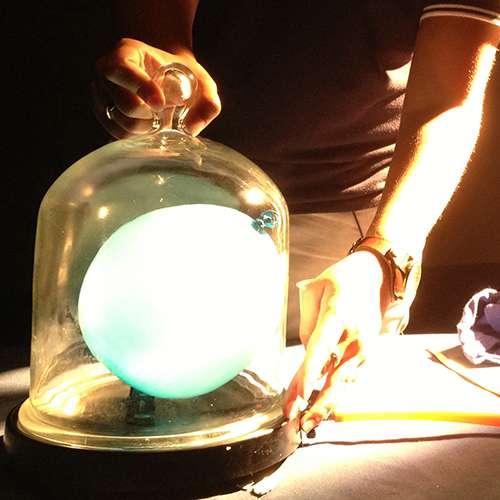 A blue balloon in bell jar under lights