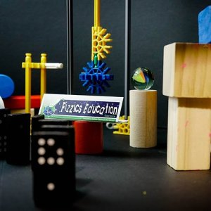 An assortment of wooden blocks, coloured plastic gears, dominoes and marbles arranged on a table with a black table cloth