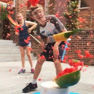 Exploding watermelon on top of a white bucket with a kid in safety glasses shouting and smiling